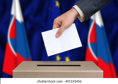 Election in Slovakia. The hand of man putting his vote in the ballot box. Slovak and European Union flags on background.