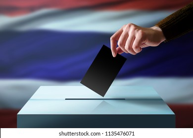 Election in Thailand Concept. Hand Dropping a Ballot Card into the Vote Box, Flag of Thai Country as background
