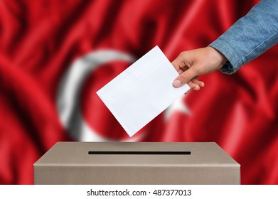 Election in Turkey. The hand of woman putting her vote in the ballot box. Turkish flag on background.