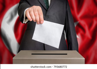 Election in Turkey - voting at the ballot box. The hand of man putting his vote in the ballot box. Flag of Turkey on background.