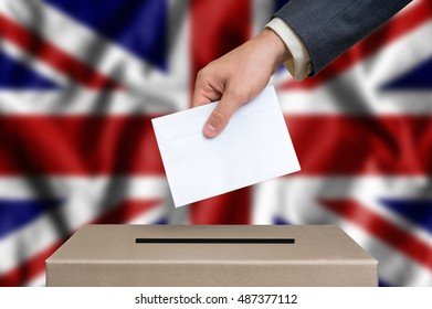 Election in United Kingdom. The hand of man putting his vote in the ballot box. United Kingdom flag on background.