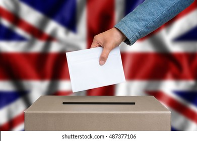 Election in United Kingdom. The hand of woman putting her vote in the ballot box. United Kingdom flag on background.