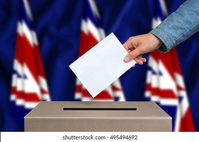 Election in United Kingdom. The hand of woman putting her vote in the ballot box. United Kingdom flags on background.