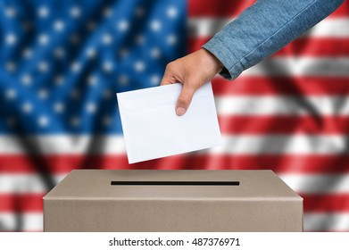 Election in United States of America. The hand of woman putting her vote in the ballot box. American flag on background.