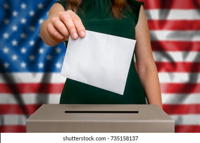Election in United States of America - voting at the ballot box. The hand of woman putting her vote in the ballot box. Flag of USA on background.