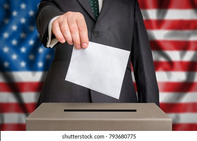 Election in United States of America - voting at the ballot box. The hand of man putting his vote in the ballot box. Flag of USA on background.