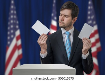 Election in USA. Undecided voter holds envelopes in hands above vote ballot and making decision. United States of America flags in background.