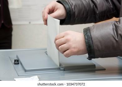 Elections. The man drops his ballot in the ballot box