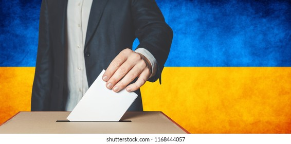 Elections in Ukraine, political struggle. Democracy, freedom and independence concept. Man Voter Putting Ballot In to Voting box