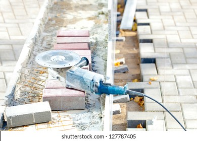 Electric angle grinder at construction building site during roadworks