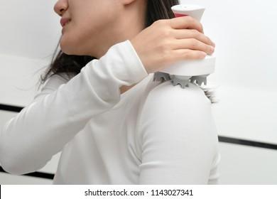 electric arm, neck and shoulder massage machine on women shoulder, closeup, healthcare and medicine concept