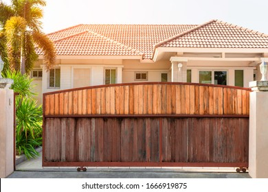 Electric automatic sliding wooden door or garage with modern home background. Auto gate and remote control concept.