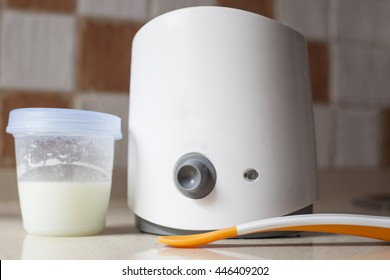 Electric baby food warmer used for heat  breast milk. Bottle and plastic spoon over kitchen countertop
