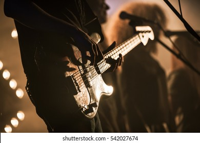 Electric bass guitar player on the stage with strobe illumination, live hard rock music theme