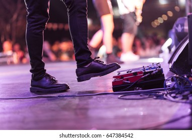 Electric bass guitar player on a stage with set of distortion effect pedals under his foot.