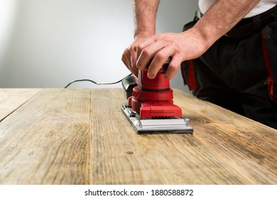 Electric belt sander, sanding machine in male hand. Processing of workpiece on light brown wooden table