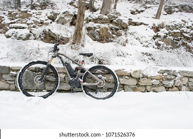 electric bicycle, e-bike, ebike, resting on a wall of rocks, snowy road, mountain forest during snowstorm, sports, end of winter, handlebars, wheel, display, cold, alps, Piedmont, Italy