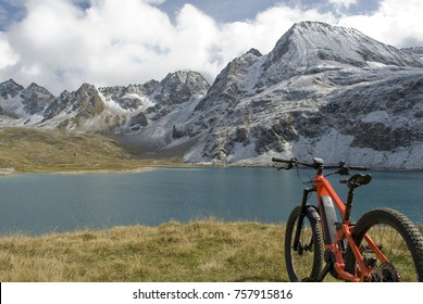 electric bicycle (orange), ebike, alpine lake, green water, in background snow covered mountains (Castel, Kastelhorn) from a fresh snowfall, Formazza valley, Autumn, clouds and sun, Piedmont, Italy