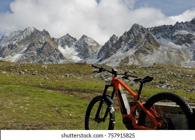 electric bicycle (orange), ebike, in a valley covered with pasture grass, snow covered mountains (Castel, Kastelhorn) from fresh snowfall of Formazza valley, Autumn, clouds and sun, Piedmont, Italy