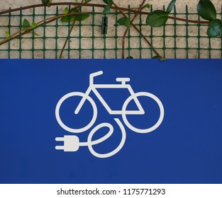 Electric bike, or e-bike, charging station sign on wall with green leaves.