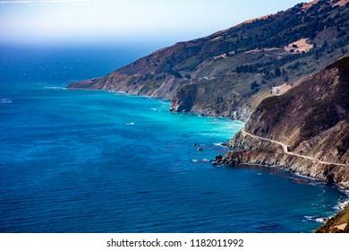 Electric blue ocean waters next to Pacific Coast Highway on California coastline Big Sur