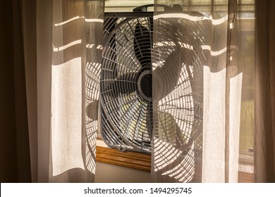 Electric Box Fan Sitting on a Window Sill with Sheer Lace Curtains.