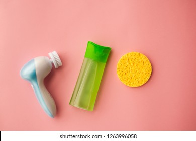 electric brush cleanser and gel for cleansing the face and a face sponge on a pink background. Facial care. Cosmetic device. Deep skin cleansing. selective focus.