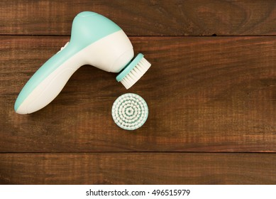 Electric brush cleanser on a wooden background.