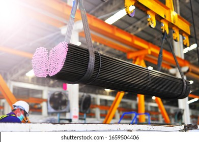 Electric Cable Hoist , heavy hoist iron hook lifting of round steel bars and place on a truck at warehouse.
