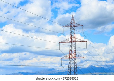 Electric cable and tower with blue sky clouds as background.