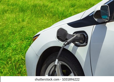 Electric car charging on parking lot with electric car charging station on background of green grass. Close up of power supply plugged into an electric car being charged. Electric car socket.