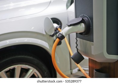 Electric car charging on parking lot with electric car charging station.