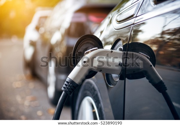 Elektrische Autovermietung auf Parkplatz mit elektrischen Autos Ladestation auf der Stadtstraße. Elektrische Autos in der Reihe, die kostenlos sind. Nahaufnahme eines Netzteils, das an ein geladenes Elektroauto angeschlossen ist.
