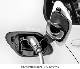 Electric car connected to a charging point with its charging lead in place