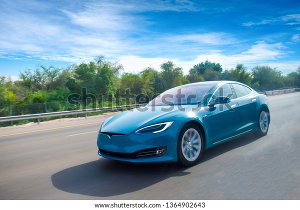 An electric car cruising on highway,with clear blue sky.green energy concept.Have space for text.