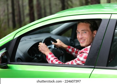 Electric car driver - green energy biofuel concept. Male behind wheel. Man driving new ecofriendly vehicle in nature forest. Young male owner proud confident looking at camera, Taxi driver concept.