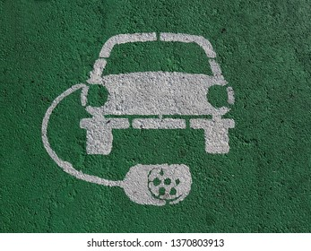 Electric car parking and charging station sign, painted on asphalt. White symbol of a car with socket plug around it on green background