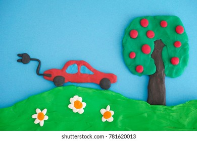 Electric Car Saving the Environment. Concept Image. Electric car, tree and field are made out of play clay (plasticine).