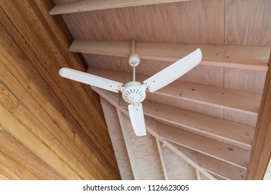A electric ceiling fan, vintage style, on woodden interior room background.