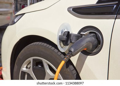 Electric charger station with power supply plugged into an electric car being charged
