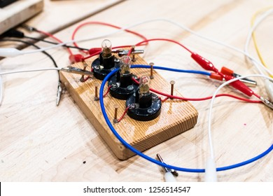 electric circuits in low voltage children, mounted on wooden bases with copper nails for alligator clips. technological education activities, STEM and electronics at school. Wires and circuits for kid