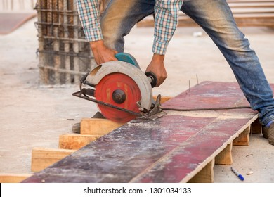 Electric circular saws are being cut plank by construction workers.