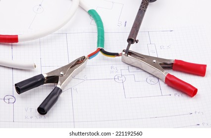 Electric clamps and a soldering iron on a background of the electric scheme