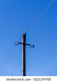 An electric concrete pillar with insulators and a stretched aluminum wire against a blue sky.