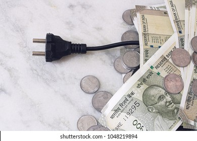 An electric cord with a fork sticks out of placer Indian money. Coins and notes of Indian rupees, like the cost of electricity. Electricity prices in India.