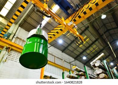Electric crane hook handling chemical barrels loading for logistics import export and transport factory.