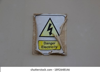 Electric danger symbol with a words DANGER ELECTRICITY. Sticker is old and peeled off and burnt-out  - Shutterstock ID 1892648146
