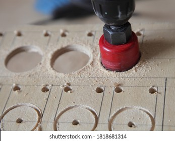 Electric drill machine with a circular drill bit close up, drilling of large diameter holes in the plywood