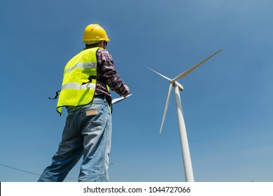 Electric Engineer writing Maintenance report on Clipboard with Wind turbine power Generator Tower Background as Green energy or Renewable Energy Technology Project Development Concept.