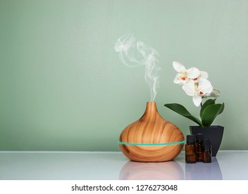 Electric Essential oils Aroma diffuser, oil bottles and flowers on light green surface with reflection.